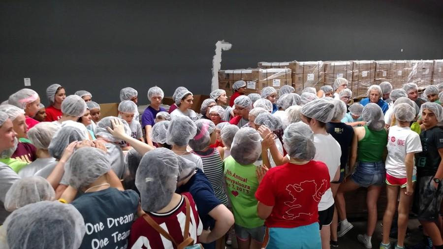 Service and Song volunteers pray over the food they just packed at Feed My Starving Children last summer.