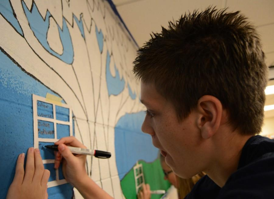 """Tom Constertina adds his name to the class mural. """"I really liked the speaker,"""" he said. """"He offered a lot of philosphical ideas."""""""