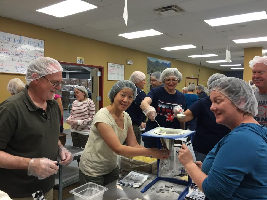Faculty members pack food for impoverished children at Feed My Starving Children.