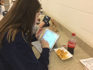 A student works on her iPad while eating lunch.