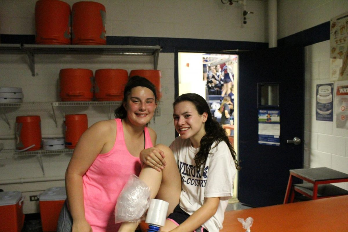 Senior+Olivia+Isufi+wraps+a+teammate%27s+leg+in+ice.%0APhoto+by+Anthony+Novak+
