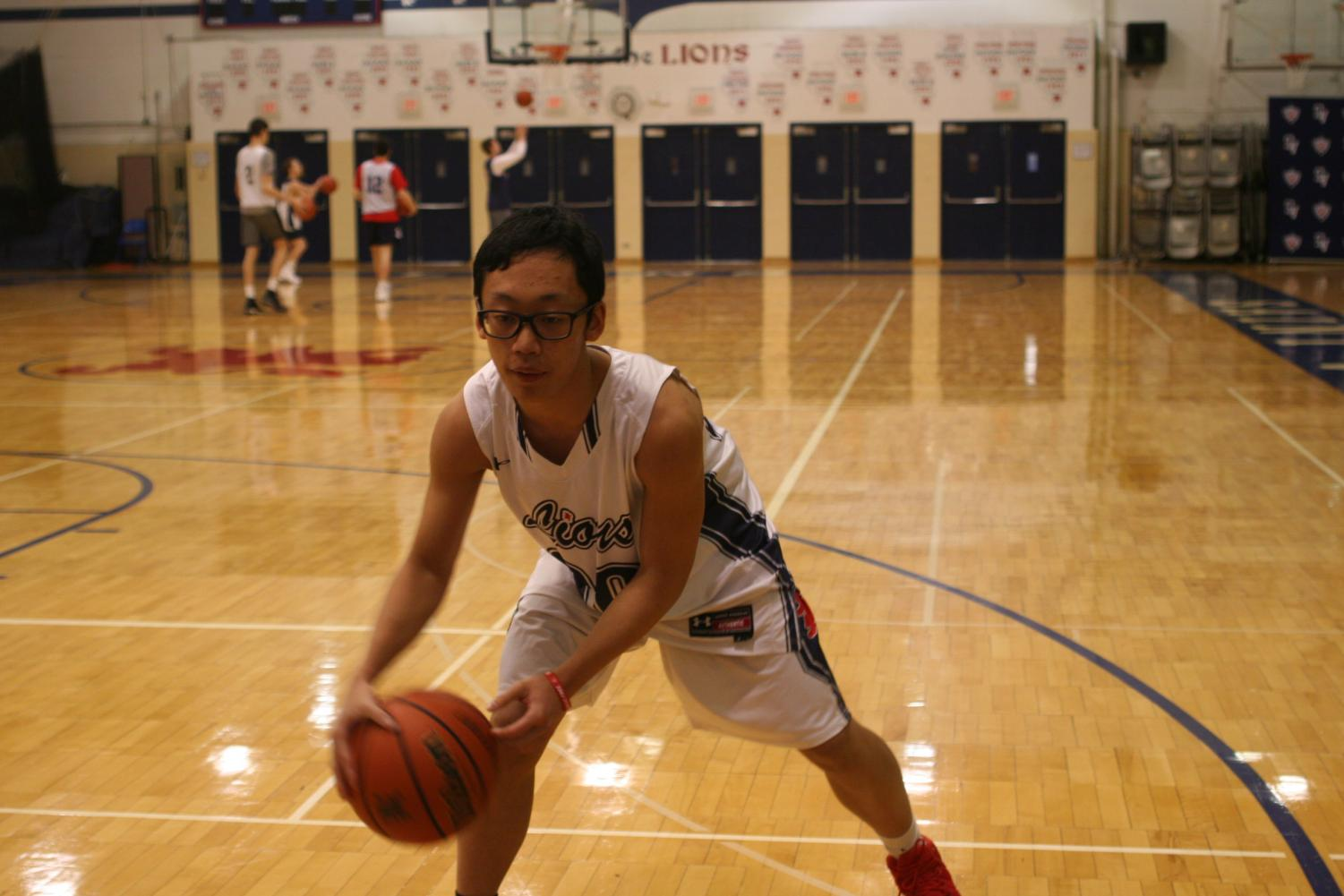 International senior Bill Huang practices his dribbling during his basketball practice.