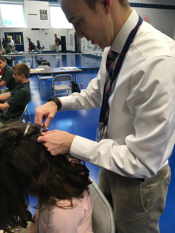 Dean Fuja cuts a student's hair for drug testing.