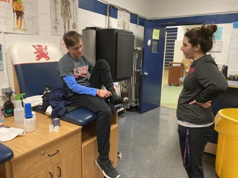 Freshman Tyler Bielfeldt works in the athletic training room with Coach Gina Garro.