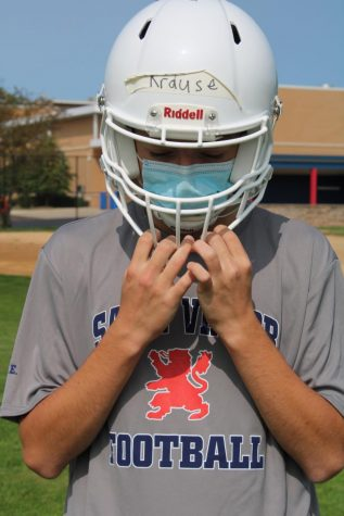 Sophomore John Krause wears a mask while practicing at a contact day.
