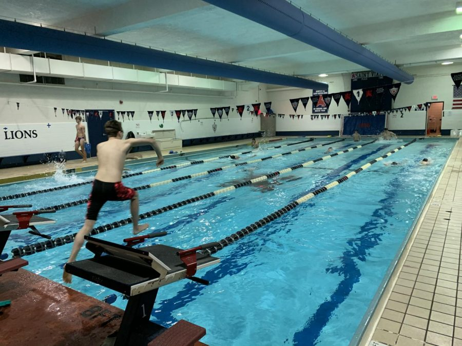 Members of boys swim team warming up at practice.